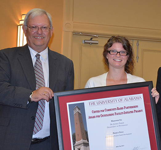 On behalf of project director Dr. Jeffrey G. Parker, Unidentified student accepts Outstanding Faculty/Staff Engagement Award for Practicum in Positive Youth Development and Civic Engagement, a partership between the UA psychology department and several community organizations working to improve the Holt community and develop student leadership.