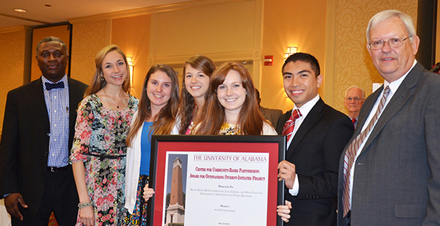 Students Kelsey Balzli, Jacquie McMahanon, Benjie Ladrillono, Julia Gardial and Haley Flanagan stand with Dr. Samory Pruitt, left, and Acting Provost Joe Benson with the certificate acknowledging their award winning ant-bullying project in the student-initiated engagment project category.