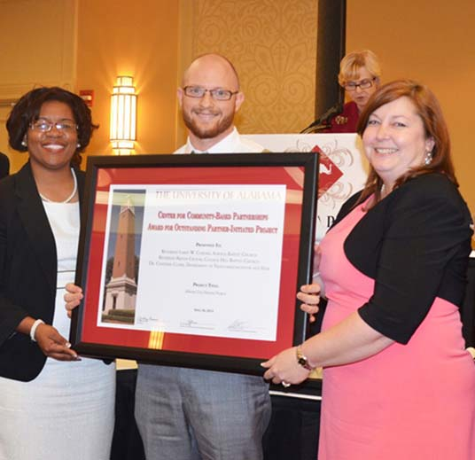 Nancy Boyd, left, representing College Hills Baptist Church and its pastor Rev Kelvin Croom, and Colby Mouchette, student pastor representing Alberta Baptist Church and Pastor Larry Corder, accept an Outstanding  Community Partner-Initiated project with Dr. Chandra Clark , right, in the TCF department of the College of Communication and Information Sciences.  They developed and carried out a plan to save community history following the April 2011 tornado. Dr. Clark's New Media class used photography, audio and video to capture Alberta City before and after the tornado.