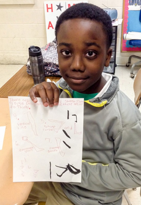 Student holds up example of Chinese calligraphy.