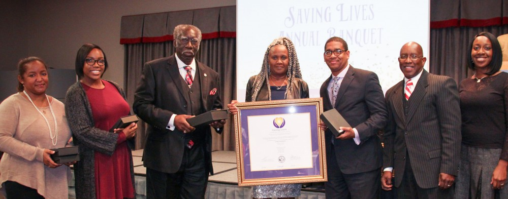 Benville Baptist Church pastor Rev. Simon Hunter (third from left) and (from left) SLI advocates Ms. Portia Jones, Ms. Ava Travis, and Ms. Annette Harris are inducted into the Saving Lives network after a year in the program. Plum Grove Baptist Church's Rev. Antonio Gardner (third from right), and Rev. Richard L. Morgan (First African Baptist Church) join the induction as pastors of the original set of churches inducted into the network. At far right is Ms. Carol Agomo, Saving Lives program coordinator.