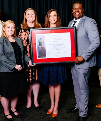 Amanda Lightsey of Tucaloosa's One Place, second from right, accepts the award for Excellence for Outstanding Community Partner-Initiated Engagement Effort for a partnership program that helps prepare prisoners in the transition from prison to the workforce.