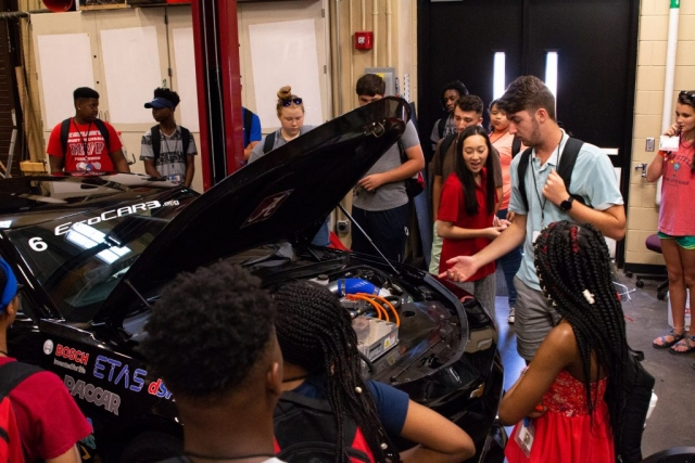 STEM Academy students experience a close encounter with EcoCAR3, guided by UA graduate student Ashley Phan.