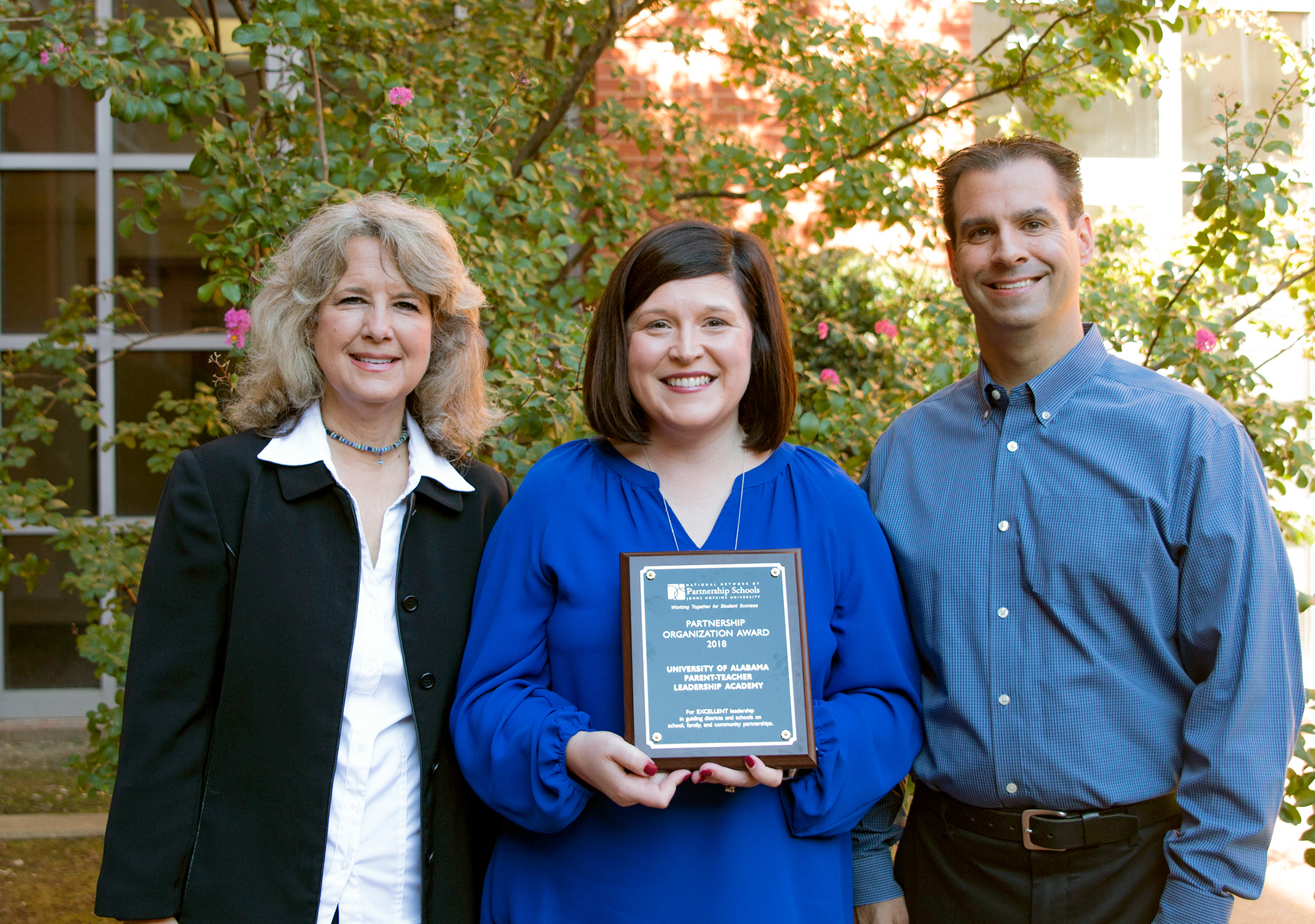 Dr. Elizabeth Wilson, Dr. Blake Berryhill, and Dr. Holly Morgan (center) are shown with the plaque recognizing UA's Parent Teacher Leadership Academy as a recipient of the Partnership Organization Award from the National Network of Partnership Schools at Johns Hopkins University. Morgan is PTLA director and Wilson and Berryhill are faculty partners representing the Colleges of Education and Human Environmental Sciences.