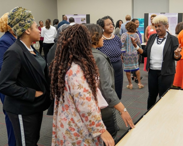 Saving Lives advocate Annette Harris, discusses community engagement project during the poster session.