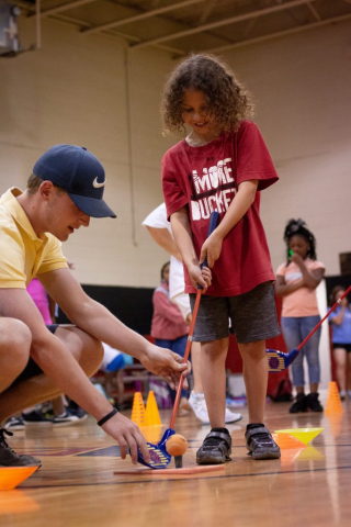 Instructor from First Tee works with a child on golf skills.
