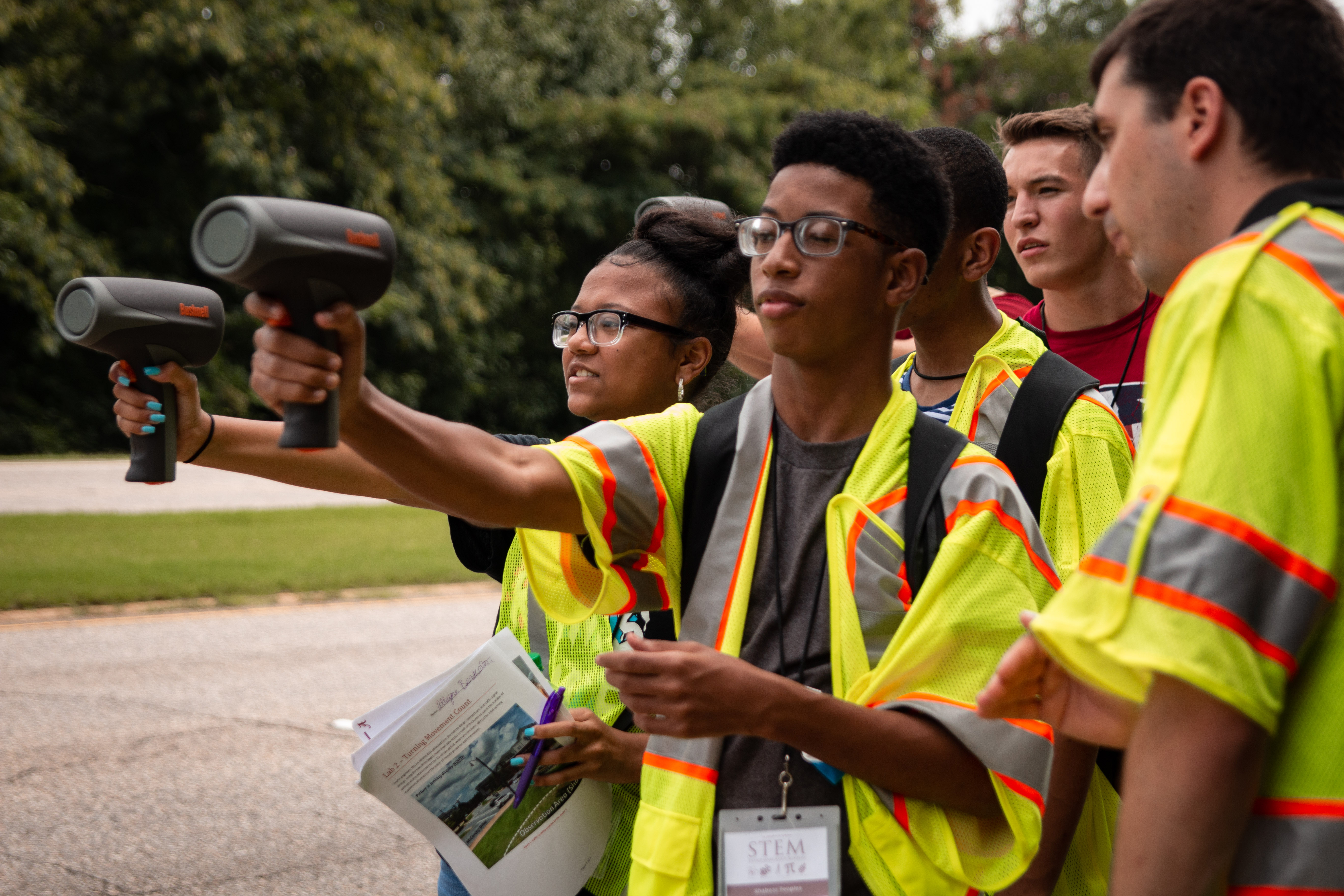 Students measure the speed of passing cars using radar guns.