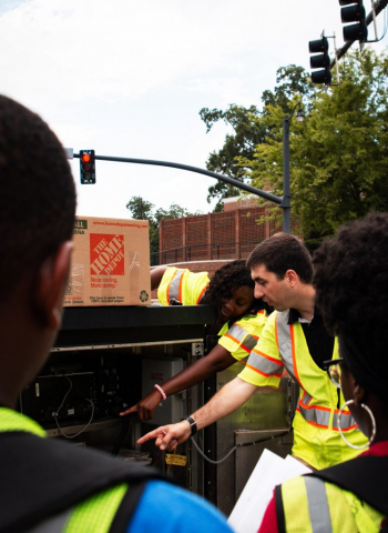 Engineering faculty member Dr. Alexander Hainen shows STEM camp students how traffic signals work.