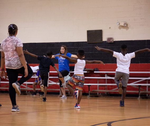 Physical education instructor Tori Ivy leads children to work on balance through yoga.
