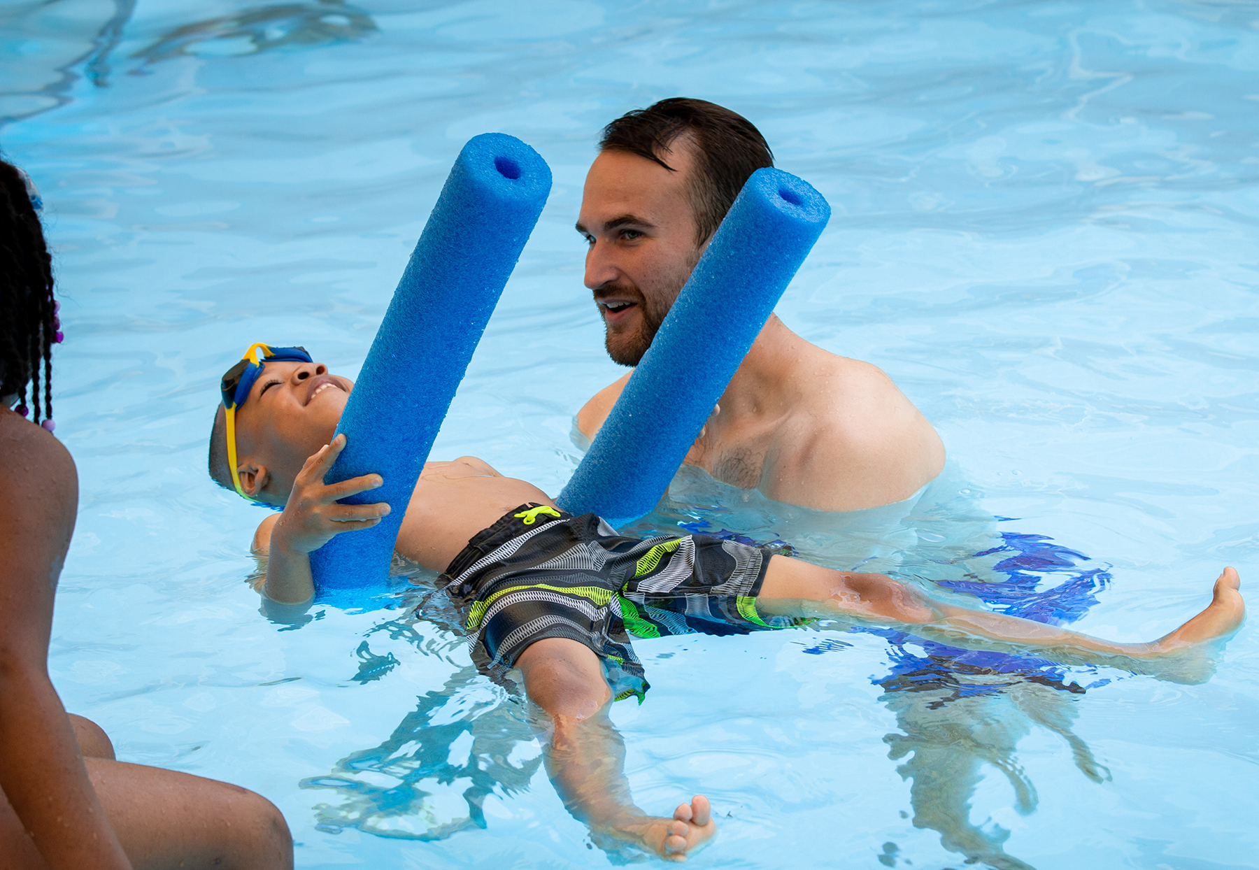Swim instructor Jake Peterson works with a child learning to float on the water.