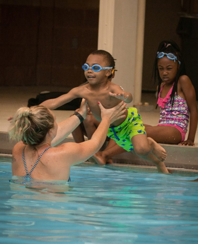 Program coordinator and swim instructor Daniela Susnara helps as a child jumps into the water.