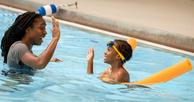 Swim instructor Kiara Williams and a child celebrate with a high five.
