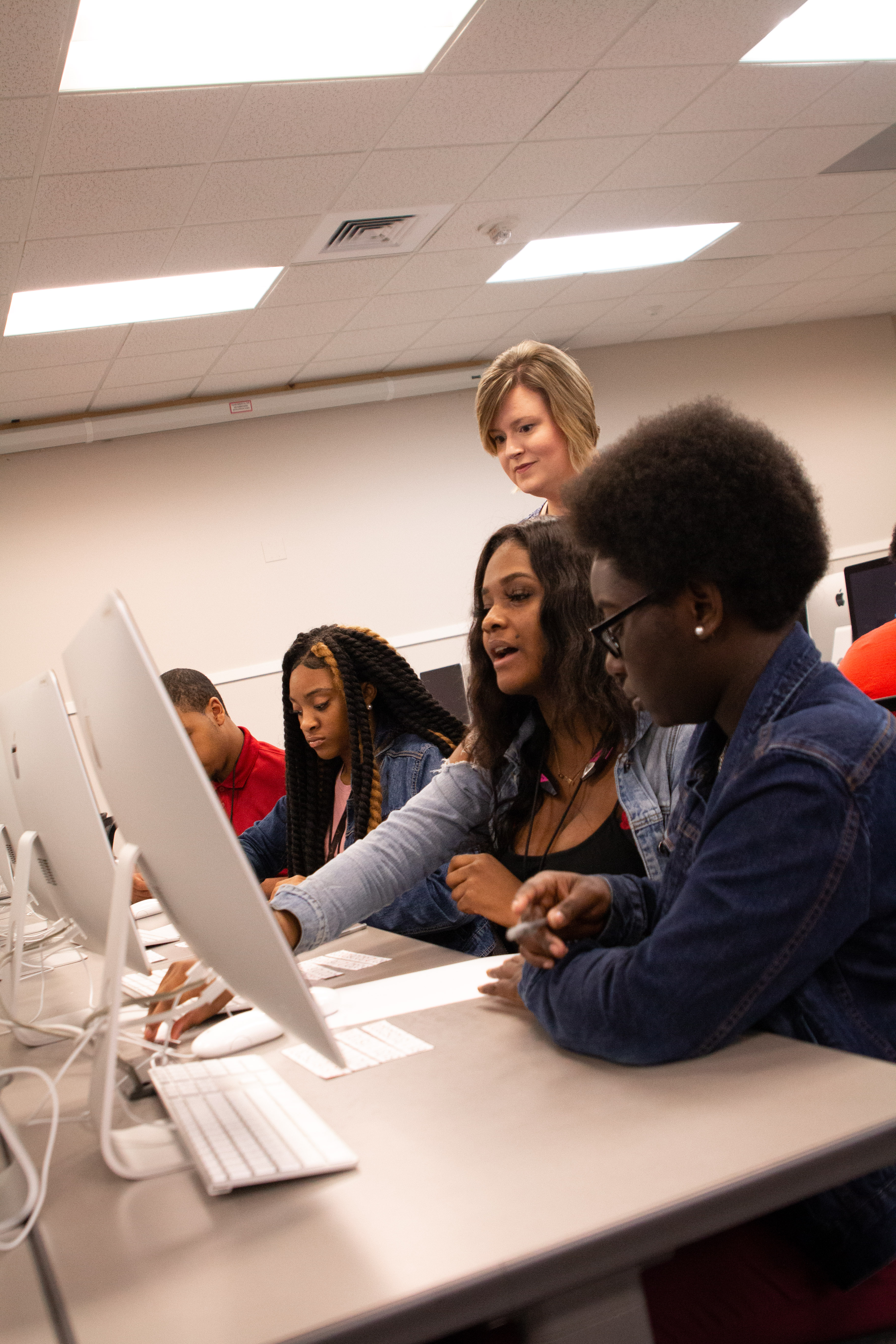 Andrea Ziegler, Center for Community-Based Partnerships director for community education, looks on as students work during the STEM Entrepreneurship Academy summer camp.