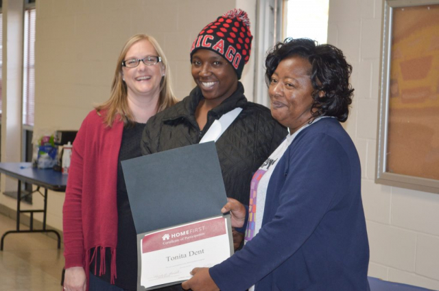 Anita Lewis, executive director of the Housing Authority of Greene County (right) and Susan Kasteler, HomeFirst program coordinator (left), present a certificate of participation to Tonita Dent.