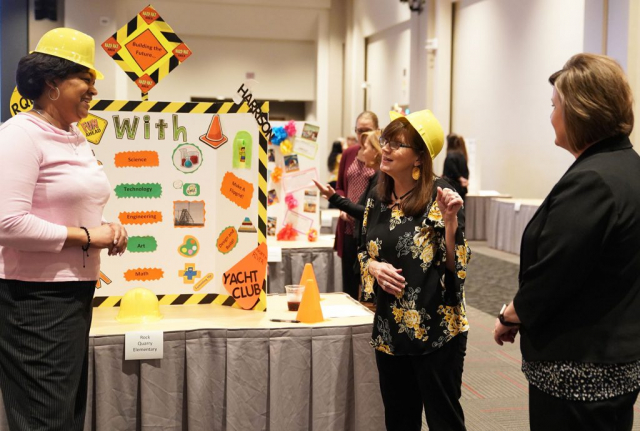 """Deniese Spencer, left, a Rock Quarry parent, and elementary fifth-grade teacher Leanna McWilliams (center) introduce their project """"Building the Future with STEAM"""" as CCBP's Andrea Ziegler looks on."""